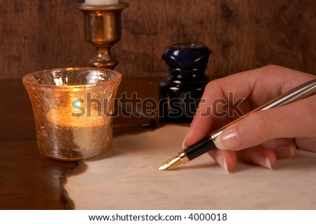 Hand writing on parchment with a golden fountain pen - stock photo