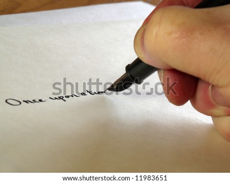 Hand writing 'Once upon a time' with fountain pen - stock photo