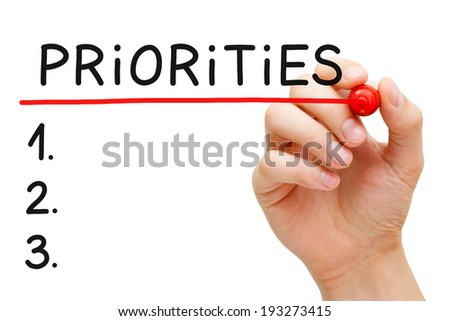 Hand writing Priorities list with marker isolated on white. - stock photo