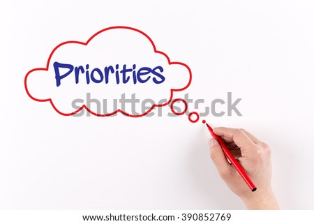 Hand writing Priorities on white paper, view from above - stock photo