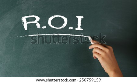 Hand writing R.O.I., the abbreviation for Return On Investments on a blackboard