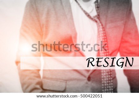 Hand writing RESIGN with the young business man on background. Business concept. Stock Photo.