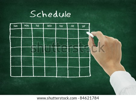 Hand writing schedule on chalkboard - stock photo