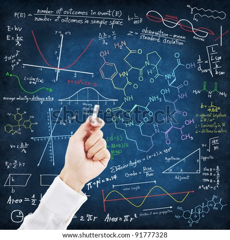 Hand writing science formulas on chalkboard - stock photo