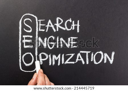 Hand writing Search Engine Optimization (SEO) topic with chalk - stock photo
