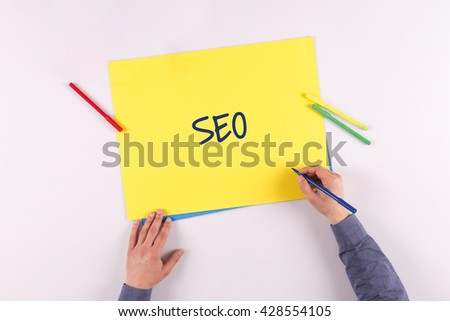 Hand writing SEO on yellow paper - stock photo