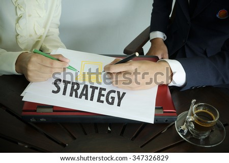 hand writing strategy text with two business person , team work concept - stock photo
