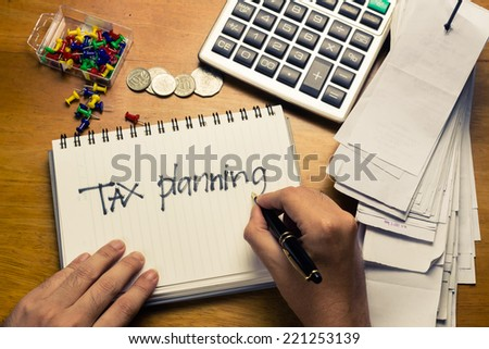 Hand writing Tax Planning word on the accountant desk - stock photo