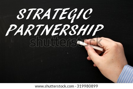Hand writing the phrase Strategic Partnership in white text on a blackboard. Companies  and people enter into Strategic Partnerships to develop business and leverage opportunities - stock photo