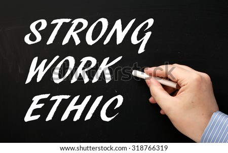 Hand writing the phrase Strong Work Ethic in white text on a blackboard as a reminder of the characteristics required for success - stock photo