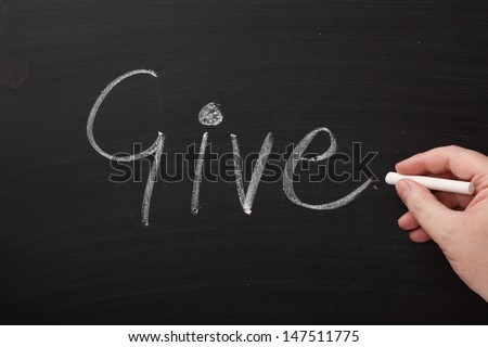 Hand writing the word Give in chalk on a used blackboard. Giving takes many forms and may involve time or money or just our presence and kind words. - stock photo