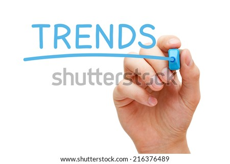 Hand writing Trends with blue marker on transparent wipe board.