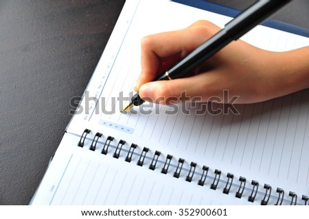Hand Writing using Fountain Pen on a notebook - stock photo