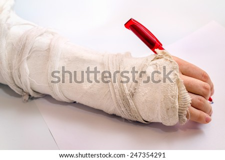hand writing with the red pen with medicine bandage on injury elbow - stock photo
