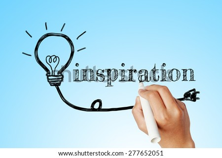 hand writing word of  INSPIRATION with lightbulb background