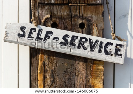 hand written self-service sign on a weathered oaken pole