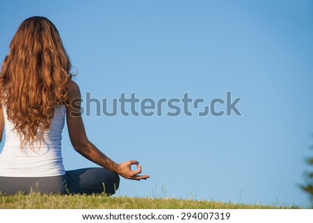 Hand yoga gesture isolated on blue background. Girl in white singlet with beutiful long hair doing meditation on the grass. - stock photo