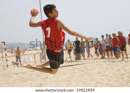 Handball player jumping with the ball trying to score a goal on a handball beach match - stock photo