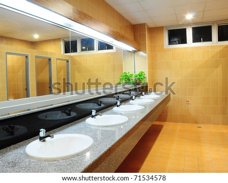 Handbasin and mirror in toilet - stock photo