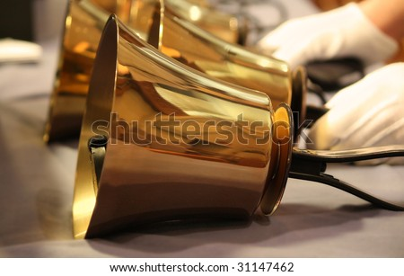 Handbells on table with gloved hands ready to perform - stock photo