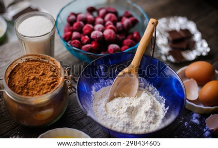 handcarved wooden spoon and cooking a cherry pie - stock photo