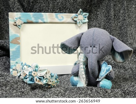 handcrafted beautiful sad baby elephant interior toy holding a blue heart made of all natural materials in set with a handmade frame in provence style and bangle bracelet on grey background - stock photo