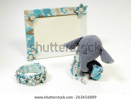 handcrafted beautiful sad baby elephant interior toy made of all natural blue materials in set with handcrafted frame and bangle bracelet in provence style - stock photo