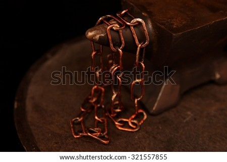 Handcrafted chain draped over an anvil - stock photo