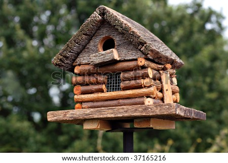 Handcrafted log cabin birdhouse.  Close-up with shallow dof. - stock photo