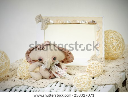 handcrafted soft toy elephant made of beige and pink natural materials with spring floral decorations and beige handmade photo frame interior background - stock photo