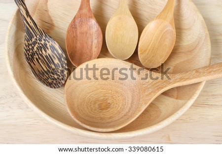 Handcrafted wooden kitchen utensils with a fork and spoons in two sizes lying on a wood surface with copyspace - stock photo