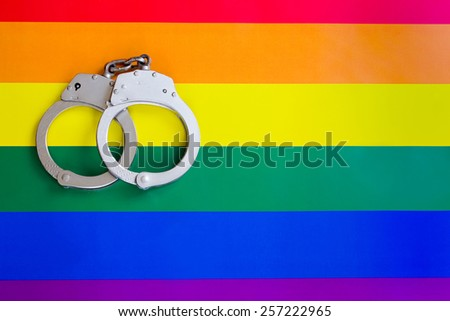 Handcuff and gay flag - stock photo