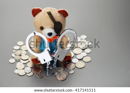 handcuff teddy bear with coins. crime concept - stock photo