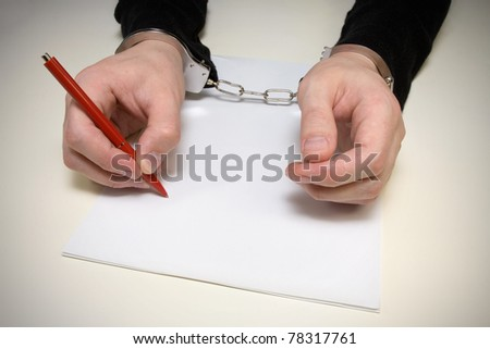 handcuffed  man  writing  a confession of the crime. - stock photo