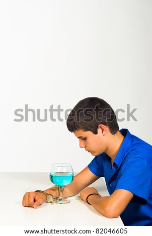 Handcuffed to a full cocktail glass, alcohol problem concept - stock photo