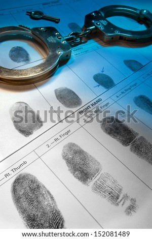 Handcuffs and fingerprint records.  - stock photo