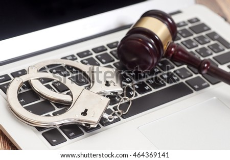 Handcuffs and gavel on laptop