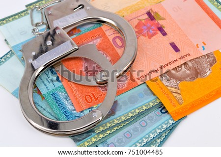 handcuffs closeup on malaysia banknote. Corruption  problem in the world. Selective focus.
