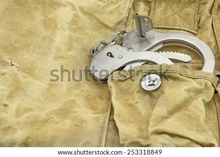 Handcuffs in The Camouflage Army Pants Pocket or Haversack or Bag or Fabric. Background  and Texture.