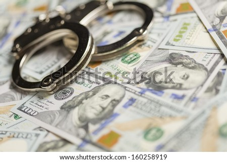 Handcuffs Laying on Newly Designed U.S. One Hundred Dollar Bills. - stock photo