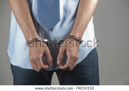 Handcuffs on a man who is arrested - stock photo