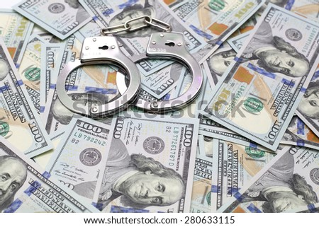 handcuffs on a pack of dollars - stock photo