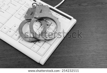 Handcuffs on computer keyboard on table - stock photo
