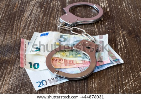 Handcuffs on euro currency, corruption or bribery concept - stock photo