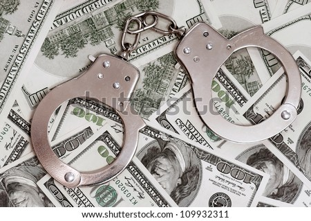 Handcuffs on money background as security concept - stock photo