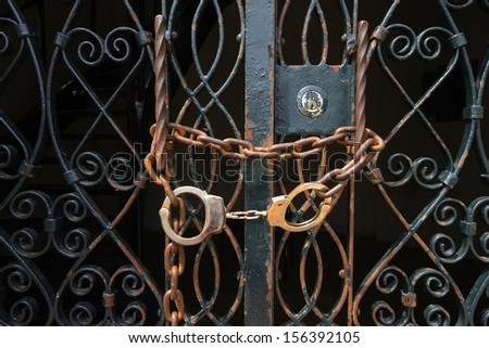 handcuffs on old iron gate - stock photo