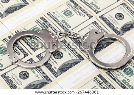 Handcuffs on one hundred dollar bills - stock photo