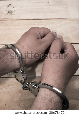 Handcuffs on the man's hands - stock photo