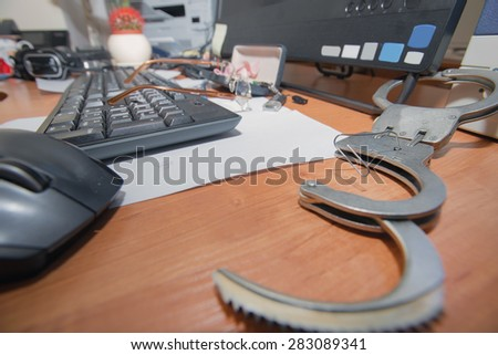Handcuffs open paper clip on the table office worker - stock photo