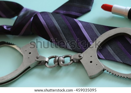 handcuffs, striped tie and lipstick